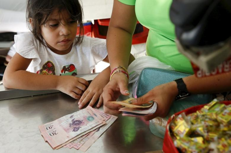 A girl looks at Venezuelan bolivar notes while her mother counts them to pay the cashier at a supermarket checkout line in Caracas, October 20, 2015.  REUTERS/Carlos Garcia Rawlins