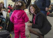 Canada's ambassador to Lebanon, Michelle Cameron, offers a teddy bear to a Syrian child at the beginning of an airlift of Syrian refugees to Canada, at the Beirut International airport December 10, 2015 in a photo provided by the Canadian military. REUTERS/Corporal Darcy Lefebvre/Canadian Forces Combat Camera/Handout via Reuters