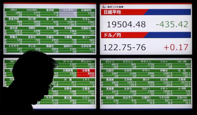 A man walks past an electronic board showing Japan's Nikkei average (top of upper right screen) and the Japanese yen's exchange rate against against the U.S. dollar outside a brokerage in Tokyo, Japan, December 4, 2015. REUTERS/Toru Hanai