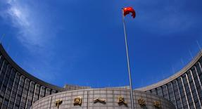 La bandera nacional china ondea frente a la sede del Banco Central, en el centro de Pekín, 16 de mayo de 2014. Los bancos chinos ofrecieron 708.900 millones de yuanes (109.830 millones de dólares) en nuevos préstamos netos en moneda local durante noviembre, ligeramente por encima de las expectativas de los economistas y sobre los 513.600 millones de yuanes del mes anterior, mostraron datos el viernes. REUTERS/Petar Kujundzic