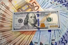 Банкноты евро и доллара США. Сараево, 9 марта 2015 года. Банк России ожидает в базовом сценарии восстановления нефтяных цен с текущих уровней до $50 за баррель в первом полугодии 2016 года и их сохранение на этом уровне до конца 2018 года, в этом случае объем чистого погашения внешнего долга частного сектора может составить порядка $30 миллиардов в 2016 году, $15 миллиардов - в 2017 году, а в 2018 году изменение внешних обязательств окажется близким к нулю или положительным. REUTERS/Dado Ruvic