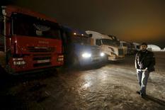 Дальнобойщик рядом с грузовиками на парковке в Московской области 3 декабря 2015 года. Президент РФ Владимир Путин предложил правительству еще раз пойти навстречу протестующим дальнобойщикам, отменив для них транспортный налог. REUTERS/Maxim Zmeyev