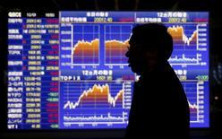 Un hombre camina delante de un tablero electrónico que muestra la información del índice Nikkei de Japón, afuera de una correduría en Tokio, Japón, 1 de diciembre de 2015. Las bolsas de Asia seguían la dirección de Wall Street y caían el viernes, mientras que las acciones japonesas se desplomaron tras saltar brevemente luego de que el Banco de Japón dijo que ampliaría partes de su programa de estímulo. REUTERS/Toru Hanai