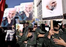 """Члены Корпуса стражей Исламской революции несут портреты бригадного генерала Хуссейна Хамедани во время его похорон в Тегеране. 11 октября 2015 года. Убийство одного из высокопоставленных командиров иранского Корпуса стражей, бригадного генерала Хуссейна Хамедани, возле сирийского города Алеппо 8 октября боевиками """"Исламского государства"""" ознаменовало начало нового этапа военного участия Ирана в Сирии, куда Тегеран, по мнению экспертов, мог направить 3.000 военных. REUTERS/Raheb Homavandi/TIMA/Files"""
