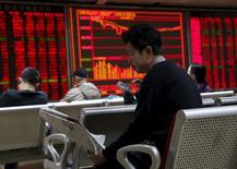 Un hombre lee un diario frente a un tablero electrónico que muestra la información de las acciones, en una correduría en Pekín, China, 17 de diciembre de 2015. Las acciones chinas revirtieron unas pérdidas iniciales y cerraron el martes con un leve avance, luego de que un fortalecimiento de los papeles ligados al sector de propiedad ayudó a impulsar al índice CSI300 de valores líderes a un nuevo máximo en cuatro meses. REUTERS/Kim Kyung-Hoon