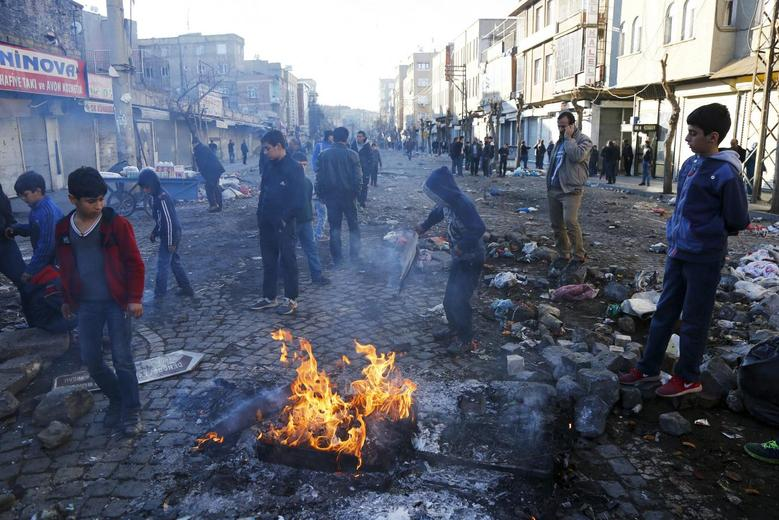 Boys stand around a fire in Sur district where clashes have taken place between Turkish security forces and Kurdish militants, in the southeastern city of Diyarbakir, Turkey, December 24, 2015. REUTERS/Sertac Kayar
