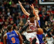 Jan 1, 2016; Chicago, IL, USA; Chicago Bulls guard Jimmy Butler (21) goes to the basket against New York Knicks forward Kyle O'Quinn (9) and forward Kristaps Porzingis (6) during the second half at United Center. The Bulls won 108-81. Mandatory Credit: Kamil Krzaczynski-USA TODAY Sports