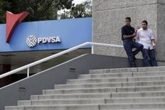 La estatal venezolana PDVSA aplazó el inicio de la exportación de gas a Colombia a consecuencia de problemas internos en la generación de energía eléctrica derivados de la variabilidad climática, informaron el viernes el Gobierno colombiano y más tarde la compañía venezolana. Imagen de archivo en la que se ve a gente en las escaleras de un edificio con el logo de en una estación de servicio en Caracas, el 28 de octubre de 2015.  REUTERS/Marco Bello