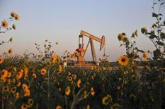 Foto de archivo de una unidad de bombeo operando cerca de Guthrie, Oklahoma, 15 de septiembre de 2015. Los precios del petróleo no subirían mucho en el 2016 ya que el débil crecimiento de la demanda no lograría absorber el alza de suministros en países como Irán e Irak, aunque se espera que la producción en naciones que no integran la OPEP se modere, mostró el lunes un sondeo de Reuters. REUTERS/Nick Oxford/Files