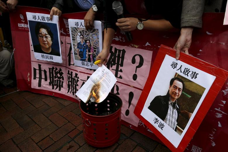 A pro-democracy demonstrator burns a letter next to pictures of missing staff members of a publishing house and a bookstore, including Gui Minhai, a China-born Swedish national who is the owner of Mighty Current,  Cheung Jiping, the business manager of the publishing house and Causeway Bay Books shareholder Lee Bo (L-R), during a protest to call for an investigation behind their disappearance, outside the Chinese liaison office in Hong Kong, China January 3, 2016. REUTERS/Tyrone Siu