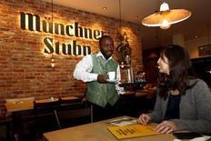 El desempleo de Alemania bajó más de lo esperado en diciembre y la tasa de desocupación se mantuvo en su menor nivel desde la reunificación en 1990, lo que deja a la mayor economía de Europa en una sólida senda al inicio del año. En la imagen se ve a Michael Abbey, de Sierra Leone, sirviendo café a su jefa Kathrin Wickenhäuser  en el 'Münchner Stubn' en Múnich el 12 de octubre de 2015. REUTERS/Michaela Rehle
