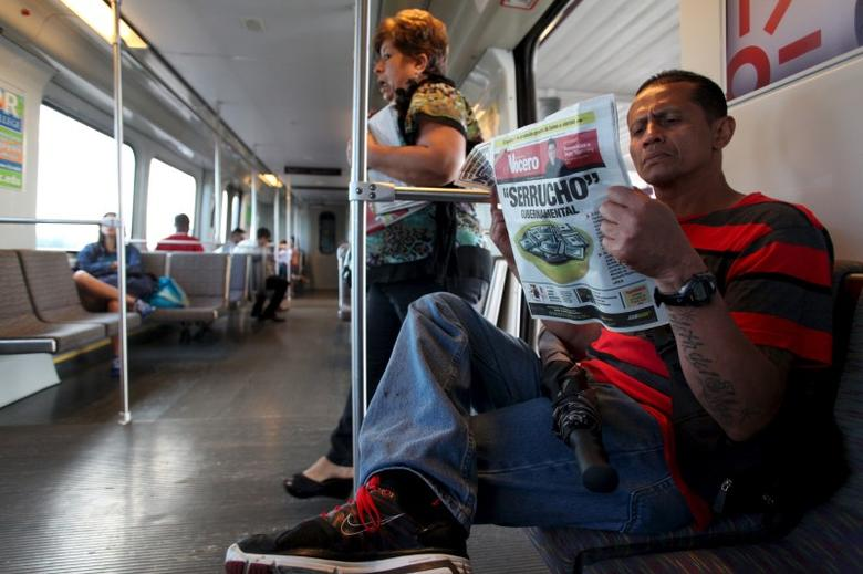 Harold Lopez (R) reads a newspaper while riding on the metro train in San Juan, December 2, 2015. REUTERS/Alvin Baez
