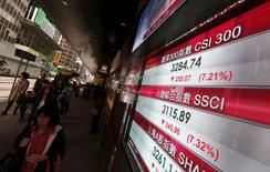 Pessoas passam por painel exibindo cotações de ações de bolsa na China, em Hong Kong. 07/01/2016 REUTERS/Bobby Yip