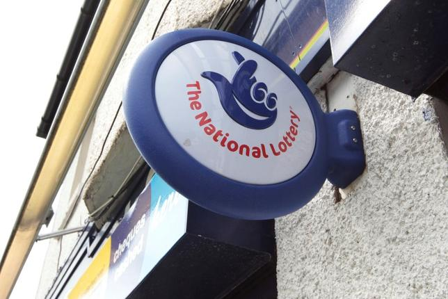 A National Lottery sign is seen over the entrance of the newsagents where EuroMillions lottery winners Colin and Chris Weir bought their winning ticket in Largs, Scotland July 16, 2011.  REUTERS/David Moir