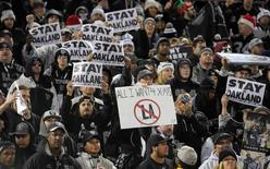 "Oakland Raiders fans hold signs that read ""Stay in Oakland"" in opposition of the Raiders potential move to Los Angeles during an NFL football game against the San Diego Chargers in Oakland, California in this December 24, 2015 file photo. Mandatory Credit: Kirby Lee-USA TODAY Sports/Files"