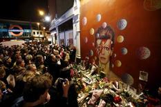 """Decenas de admiradores rinden tributo el lunes al fallecido David Bowie en Brixton, en el sur de Londres. Ene 11, 2016.  David Bowie, la estrella británica del rock que creó éxitos de la talla de """"Space Oddity"""" a través de personajes que marcaron tendencia como """"Ziggy Stardust"""", murió a los 69 años apenas dos días después de publicar un nuevo disco que aparece como un regalo de despedida. REUTERS/Peter Nicholls"""