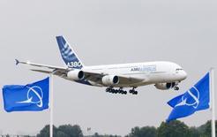 Самолет Airbus A380 пролетает мимо флагов с логотипом Boeing во время авиасалона в Ле-Бурже. 15 июня 2015 года. Европейский авиапроизводитель Airbus опередил Boeing в борьбе за новые заказы в прошлом году, расширив свой общий портфель заказов до рекордного $1 триллиона, однако отстал в поставках, в то время как Boeing укрепил свое лидерство в качестве крупнейшего авиапроизводителя. REUTERS/Pascal Rossignol