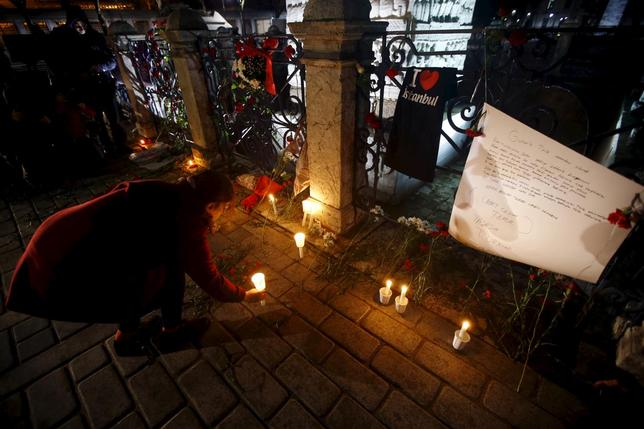 A woman places a candle at the site of Tuesday's suicide bomb attack at Sultanahmet square in Istanbul, Turkey January 13, 2016. REUTERS/Osman Orsal