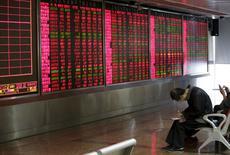Un inversor toma notas de las acciones frente a un tablero electrónico en una correduría en Pekín, China, 8 de enero de 2016. Las dos bolsas chinas dijeron el miércoles por la noche que incrementaron la monitorización de las actividades de ventas de acciones por parte de los principales accionistas de empresas. REUTERS/Jason Lee