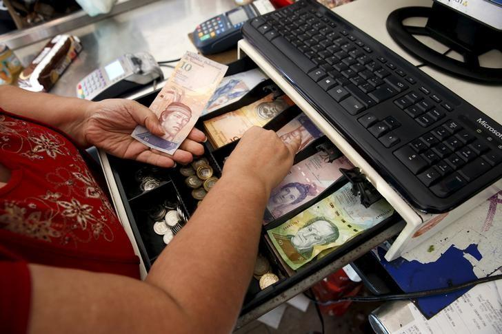 A cashier counts Venezuelan bolivar notes at a supermarket checkout line in Caracas October 20, 2015. REUTERS/Carlos Garcia Rawlins