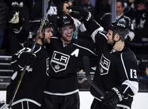 Dec 1, 2015; Los Angeles, CA, USA; Los Angeles Kings center Anze Kopitar (11) celebrates with defenseman Alec Martinez (27)  and left wing Kyle Clifford (13) after scoring the winning goal in overtime against the Vancouver Canucks at Staples Center. The Kings won 2-1 in overtime. Mandatory Credit: Kirby Lee-USA TODAY Sports