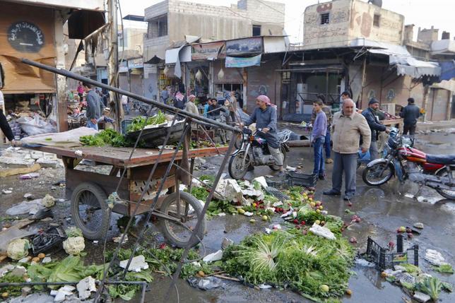 People inspect a site after hit by what activists said were air strikes by forces loyal to Syria's President Bashar al-Assad in Raqqa, November 25, 2014.  REUTERS/Nour Fourat