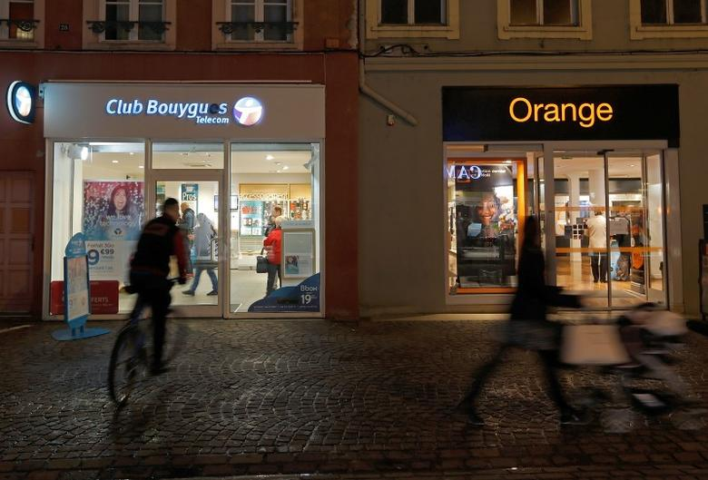Passerby walk past shops of French telecom operators Bouygues Telecom and Orange in Montbeliard, France, January 5, 2016.  REUTERS/Vincent Kessler