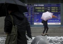 Peatones caminan delante de un tablero electrónico que muestra la información del índice Nikkei de Japón, afuera de una correduría en Tokio, Japón, 18 de enero de 2016. Las acciones japonesas cayeron el lunes en medio de la inquietud sobre las perspectivas económicas de China y el declive de los precios del crudo a mínimos no vistos desde el 2003. REUTERS/Yuya Shino