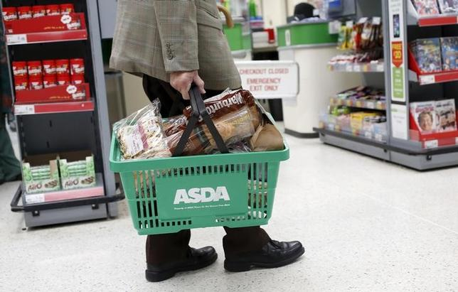 A man carries a shopping basket in an Asda store in northwest London, Britain in this August 18, 2015 file photo. Asda is expected to report Q3 results this week.   REUTERS/Suzanne Plunkett/Files