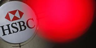 A traffic light shines red near the HSBC bank logo, pictured at the bank buidling in Paris, June 15, 2015. REUTERS/Christian Hartmann