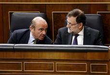 """El ministro de Economía español en funciones, Luis de Guindos, dijo el martes que los datos de los que dispone su departamento hasta ahora apuntan a que el déficit español en 2015 """"convergerá"""" al objetivo del 4,2 por ciento del PIB fijado por Bruselas. En la imagen, el presidente del Gobierno español en funciones, Mariano Rajoy (D), habla con su ministro de Economía, Luis de Guindos, en el Congreso de los Diputados en Madrid, el 15 de julio de 2015. REUTERS/Paul Hanna"""