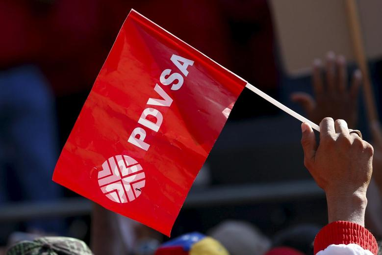 A worker of the Venezuelan state oil company PDVSA holds a flag with the company logo, during a meeting with Venezuela's President Nicolas Maduro outside Miraflores Palace in Caracas January 12, 2016.  REUTERS/Carlos Garcia Rawlins
