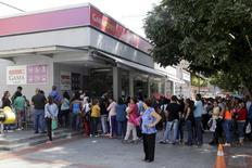 Personas hacen final para intentar comprar cómida y artículos básicos, afuera de un supermercado en Caracas, 19 de enero de 2016. Varias corporaciones importantes estadounidenses posiblemente informen en los próximos días si van a asumir grandes pérdidas por sus operaciones en Venezuela, y algunas hasta podrían anunciar que abandonarán el país sudamericano. REUTERS/Marco Bello