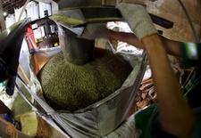 Trabalhador carrega saco com 1 tonelada de grãos de café para exportação em armazém em Santos, Brasil. 10 de dezembro de 2015. REUTERS/Paulo Whitaker