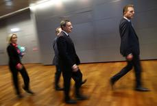Mario Draghi (au centre) à son arrivée jeudi au siège de la Banque centrale européenne à Francfort. Selon le président de la BCE, les turbulences sur les marchés financiers et les inquiétudes suscitées par les pays émergents, Chine en tête, conduiront l'institution européenne à revoir sa politique monétaire en mars. Cela alimente l'espoir de nouvelles mesures de soutien dans moins de deux mois. /Photo prise le 21 janvier 2016/REUTERS/Kai Pfaffenbach