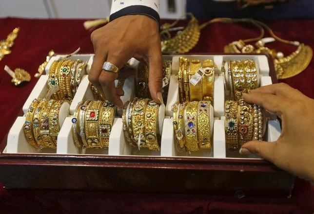 A salesman helps a customer (R) to select gold bangles at a jewelry showroom in Mumbai, May 21, 2015. REUTERS/Shailesh Andrade/Files