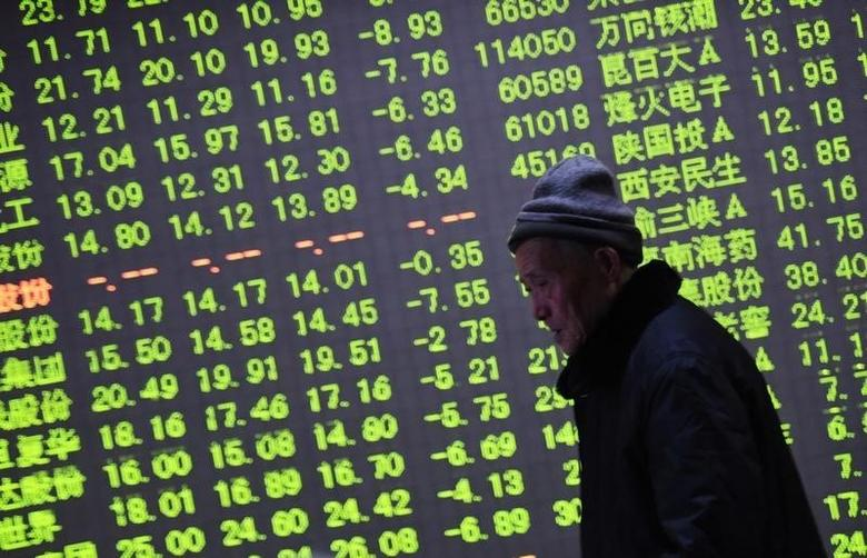 An investor walks past an electronic screen showing stock information at a brokerage house in Hangzhou, Zhejiang province, January 21, 2015.  REUTERS/China Daily