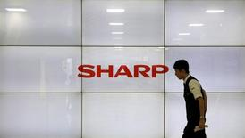 A man walks past display showing a logo of Sharp Corp in Tokyo, Japan, October 30, 2015.  REUTERS/Toru Hanai