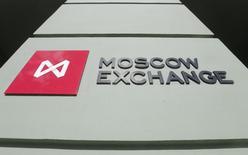 Логотип на здании Московской биржи 14 марта 2014 года. Российские фондовые индексы развернулись в начале торгов понедельника в отрицательную зону вслед за аналогичным движением нефтяных котировок. REUTERS/Maxim Shemetov