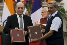Le ministre français de la Défense, Jean-Yves Le Drian, et son homologue indien Manohar Parrikar à New Delhi lors de la cérémonie de signature du protocole d'accord portant sur l'achat de 36 avions Rafale. Au deuxième jour de sa visite en Inde, François Hollande a déclaré que les questions financières qui restent à régler dans le contrat Rafale le seraient dans les prochains jours. /Photo prise le 25 janvier 2016/REUTERS/Adnan Abidi