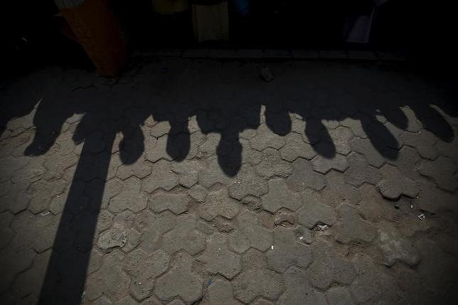 Shadows of supporters of Madhesi groups are cast on the ground as they observe minutes of silence in memory of people killed in the Madhesh protests in Kathmandu, Nepal November 23, 2015. REUTERS/Navesh Chitrakar