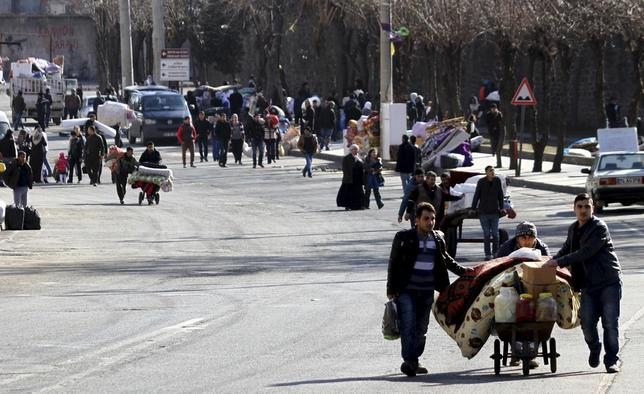 Residents carry their belongings as they flee from Sur district, which is partially under curfew, in the Kurdish-dominated southeastern city of Diyarbakir, Turkey January 27, 2016. REUTERS/Sertac Kayar
