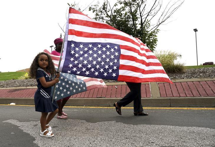 A girl carries an upside down U.S. flag during a protest march in Ferguson, Missouri August 8, 2015. REUTERS/Rick Wilking