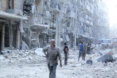 """Жители у разрушенных бомбардировкой домов в Алеппо 17 сентября 2015 года. Сирийская оппозиция обвинила ответственных за """"бомбардировки и голод мирных жителей"""" в препятствовании началу мирных переговоров, которые ООН хочет созвать в пятницу. REUTERS/Abdalrhman Ismail"""