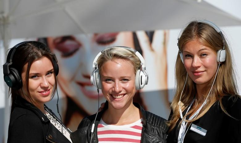 Models pose with the AKG K545 (L-R), JBL Synchros S300 and Harman/Kardon Soho headphones at the IFA consumer electronics fair in Berlin, September 6, 2013.    REUTERS/Fabrizio Bensch