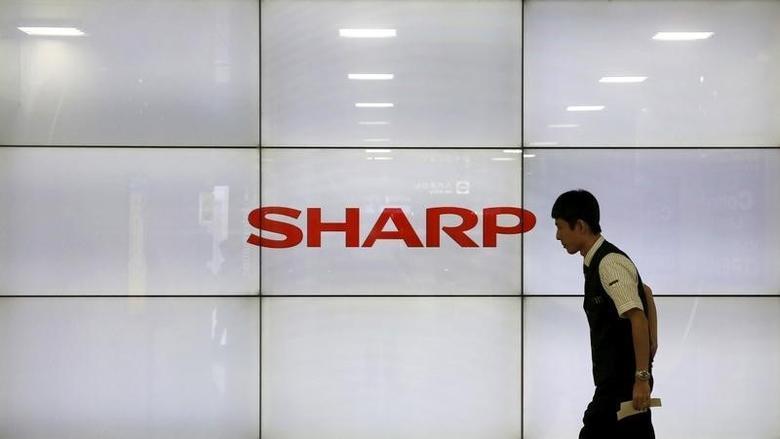 A man walks past display showing a logo of Sharp Corp in Tokyo, Japan, October 30, 2015.  REUTERS/Toru Hanai