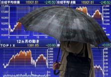 Un peatón con un paraguas camina junto a un tablero electrónico que muestra la reciente fluctuación del índice Nikkei de Japón, afuera de una correduría en Tokio, Japón. 18 de enero de 2016. El índice Nikkei de la bolsa de Tokio subió el lunes a un máximo de cierre en casi un mes, impulsado por la decisión del Banco de Japón de adoptar tasas de interés negativas la semana pasada. REUTERS/Yuya Shino