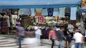 Pesonas caminan delante de una tienda en una calle comercial en el centro de Sao Paulo, 4 de diciembre de 2014. Las expectativas de inflación en Brasil siguieron subiendo para este año y al próximo después de que el Banco Central sorprendió a los mercados al mantener las tasas de interés estables en enero, mostró el sondeo semanal Focus de la entidad entre instituciones financieras. REUTERS/Paulo Whitaker