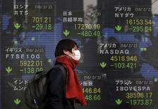 A pedestrian walks past an electronic board showing the stock market indices of various countries outside a brokerage in Tokyo, Japan, February 3, 2016.REUTERS/Yuya Shino
