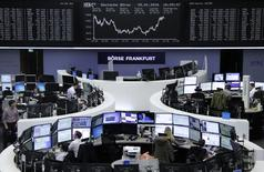 Traders work at their desks in front of the German share price index, DAX board, at the stock exchange in Frankfurt, Germany, January 29, 2016. REUTERS/Staff
